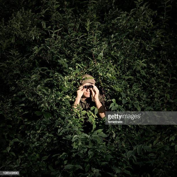 Man with binoculars hidden in bush