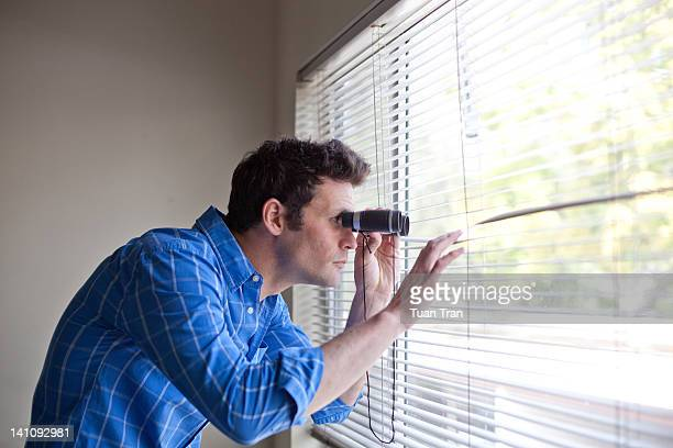 Man with binoculars looking out window