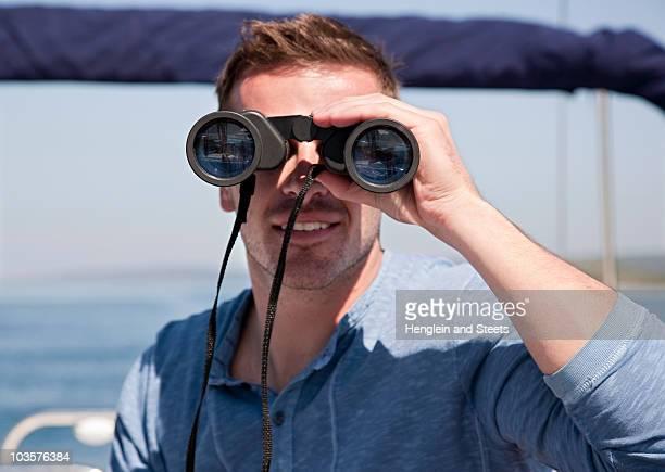 Man with binoculars on yacht