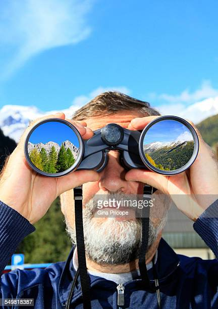 Man with binoculars sees landscapes in South Tyrol