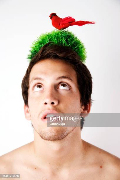 Man with Bird Standing in Grass on Top of  Head
