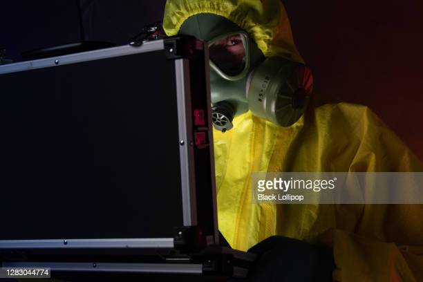 man with black briefcase in protective hazmat suit, conspiracy theory concept. - conspiracy stock pictures, royalty-free photos & images