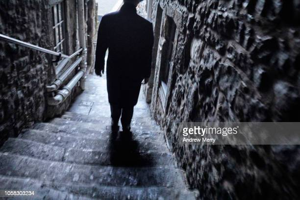 man with black coat walking down a narrow alley, footpath, thoroughfare from the royal mile, edinburgh - old town stock pictures, royalty-free photos & images
