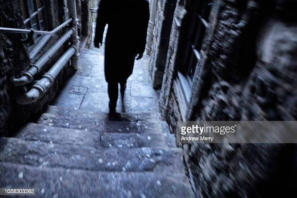 Man with black coat walking down a narrow alley, footpath, thoroughfare from the Royal Mile, Edinburgh