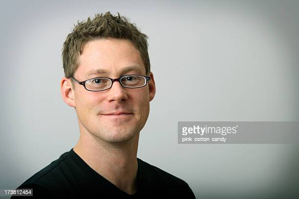 A man with black glasses and a black shirt smiling