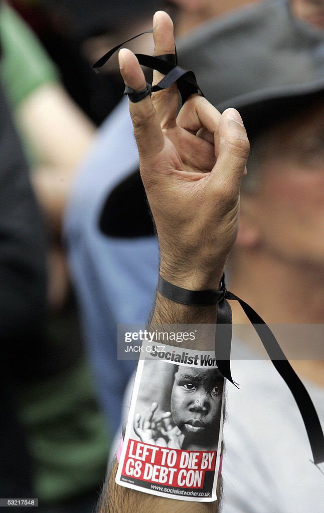 A man, with black ribbons tied to his fingers and wrist, makes the V sign while observing a minute of silence, 09 July 2005, to remember the victims of the London bombings that killed at least 50 people and injured some 700.