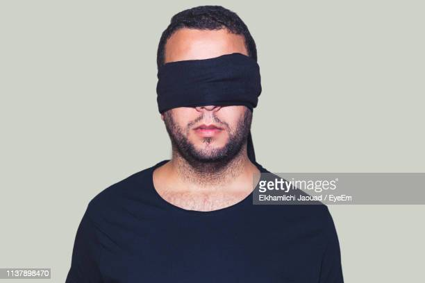 https://media.gettyimages.com/photos/man-with-blindfold-standing-against-white-background-picture-id1137898470?s=612x612