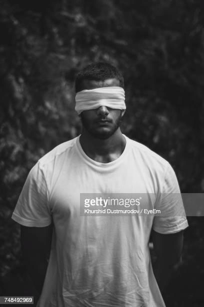 man with blindfold standing outdoors - blindfolded stock photos and pictures