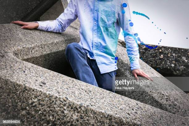 man with blue dyed clothes coming out of tetrapod - trigone foto e immagini stock