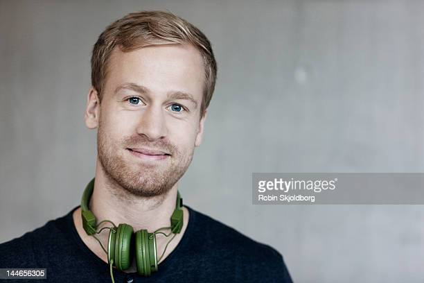 Man with blue eyes with headphones smiling.