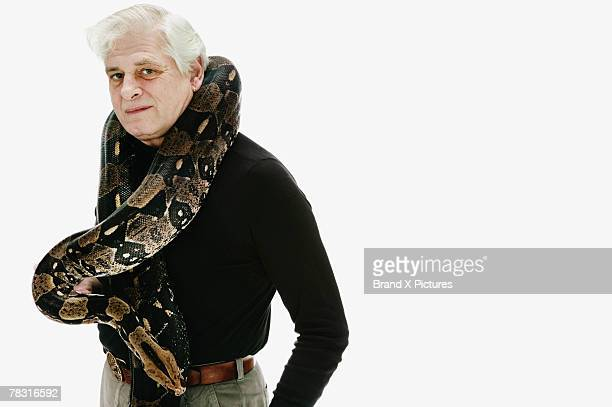 man with boa constrictor - boa constrictor stock photos and pictures