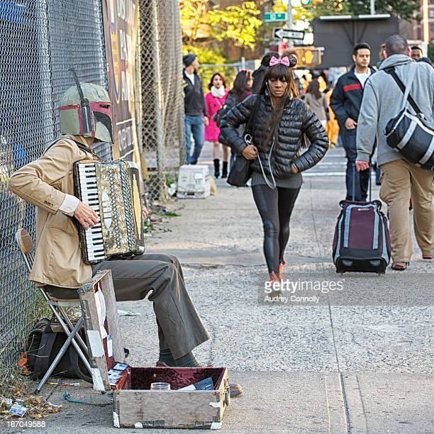 CONTENT] Man with Boba Fett helmet plays accordion on the street of Manhattan New York City during NYComicCon