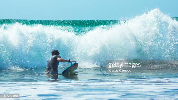 man with bodyboard in front of a crashing wave - parque nacional de santa rosa fotografías e imágenes de stock