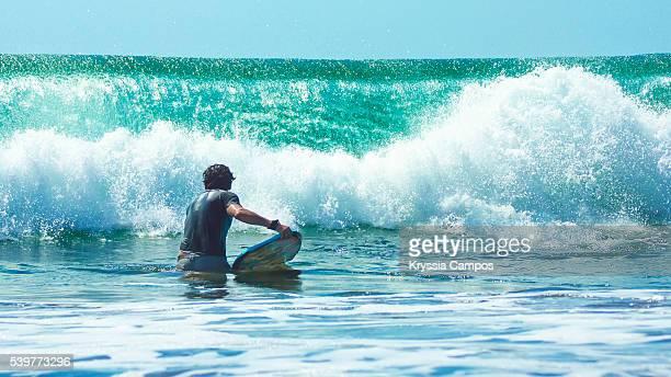 man with bodyboard on beach in front of big wave - parque nacional de santa rosa fotografías e imágenes de stock