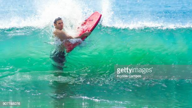 man with bodyboard through breaking wave - parque nacional de santa rosa fotografías e imágenes de stock