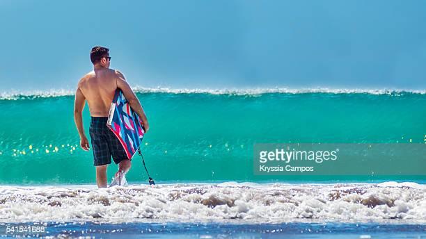man with bodyboard walking through shallow surf - parque nacional de santa rosa fotografías e imágenes de stock
