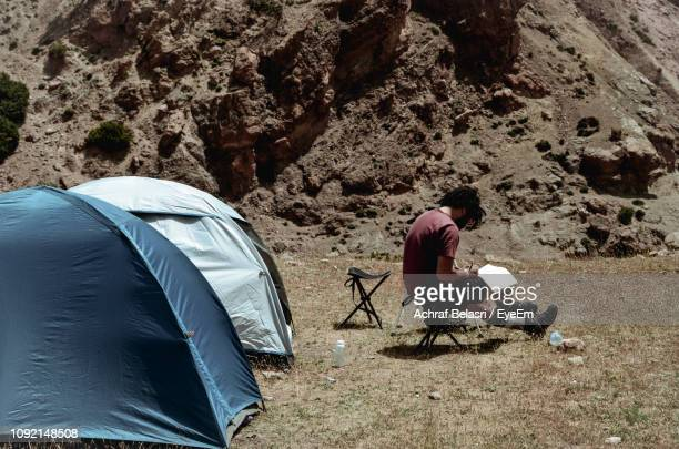 Man With Book Sitting By Tents On Field