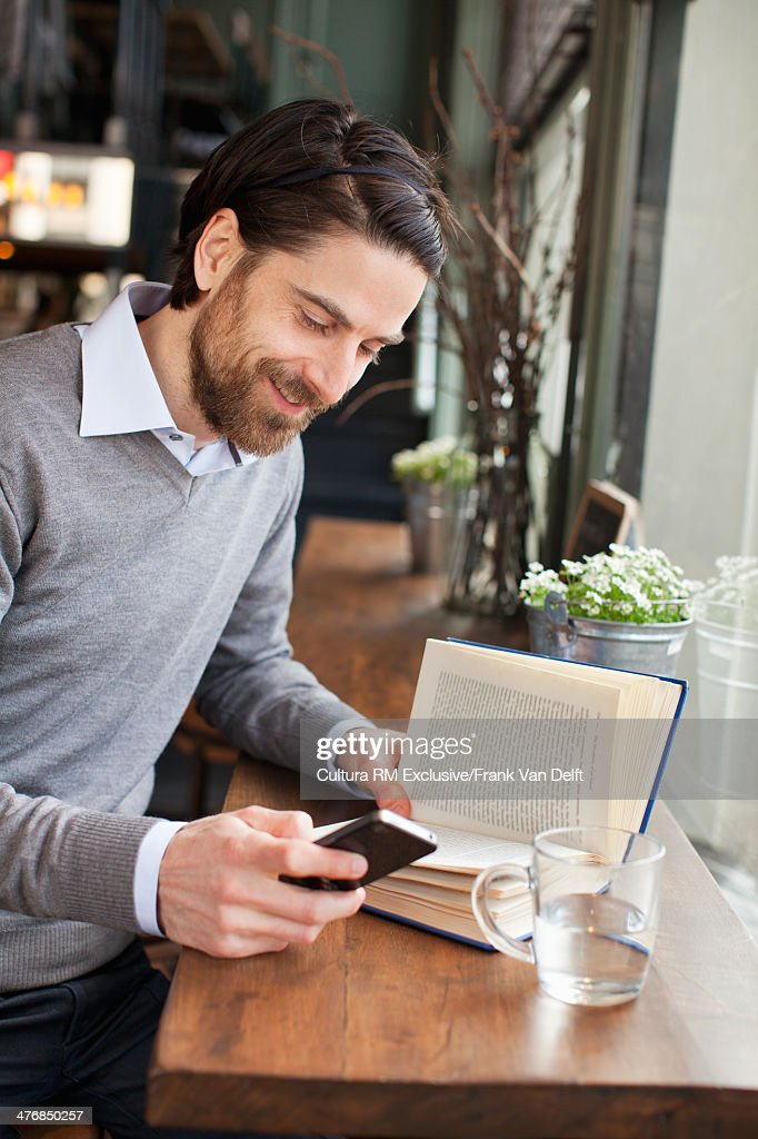 Man with book using smartphone in cafe : Stock Photo