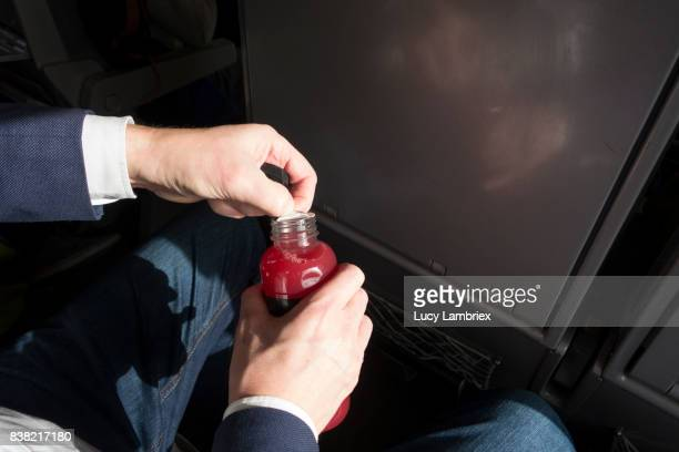 Man with bottle of juice on train