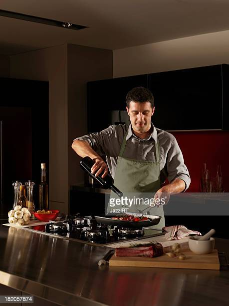 Man with bottle of wine tilting pan on stove