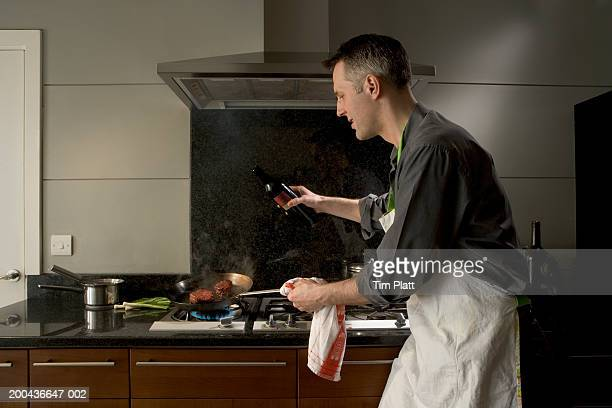 Man with bottle of wine tilting pan on stove, side view