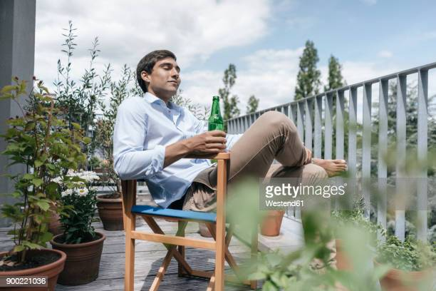 Man with bottle relaxing on balcony