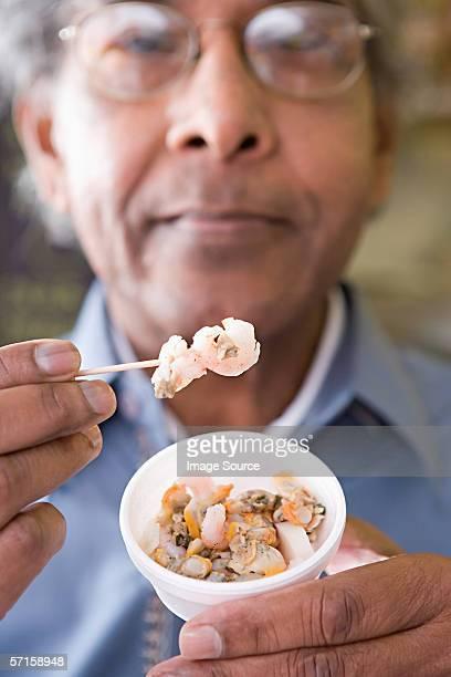 Homme avec coupe de fruits de mer