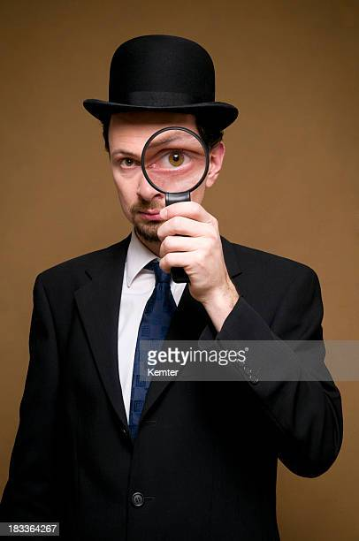 man with bowler looking through a magnifier