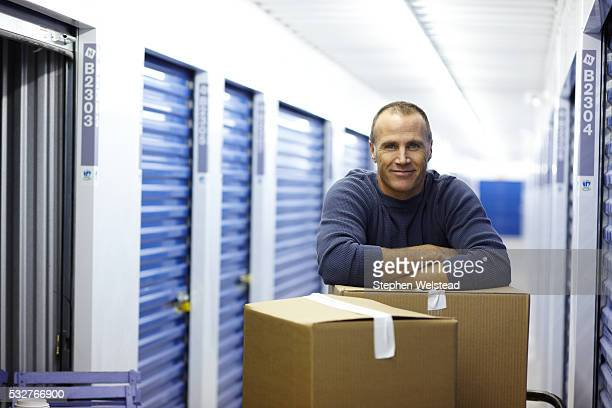 man with boxes in a storage facility - self storage stock pictures, royalty-free photos & images