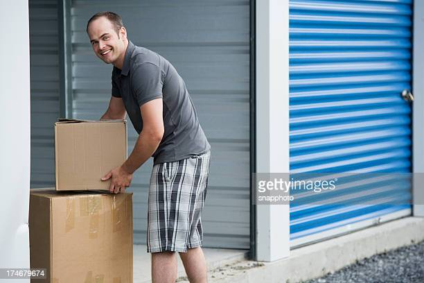 man with boxes outside self storage unit lifestyle - storage compartment stock pictures, royalty-free photos & images
