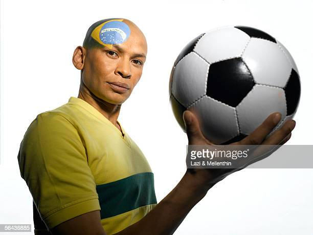 Man with Brazilian flag painted on his face, holding soccer ball, low angle view, portrait