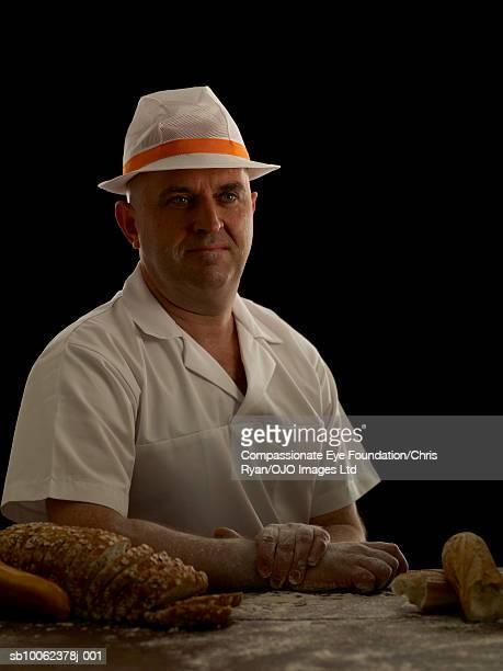 """man with bread on desk, looking away - """"compassionate eye"""" fotografías e imágenes de stock"""