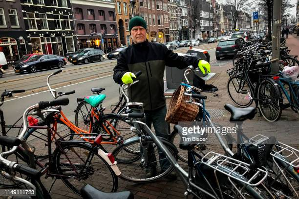 man with bright day-go gloves by bikes in amsterdam - noord holland stockfoto's en -beelden