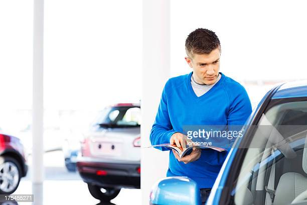 Man With Brochure Looking At Car