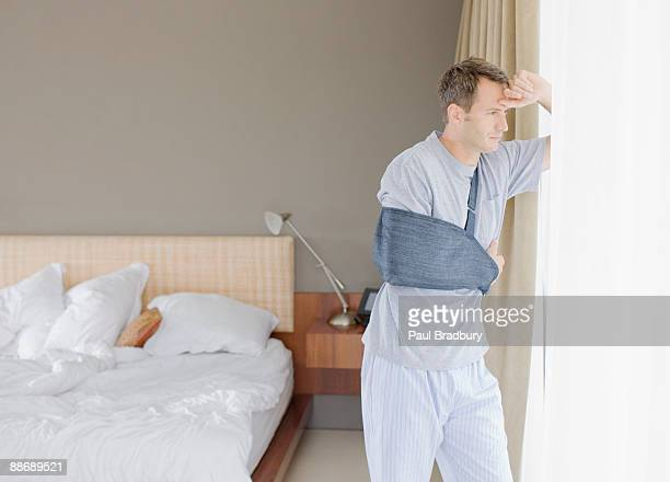 man with broken arm looking out window - arm sling stock pictures, royalty-free photos & images