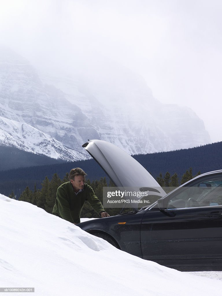 Man with broken car in snow, mountains in background : Stockfoto