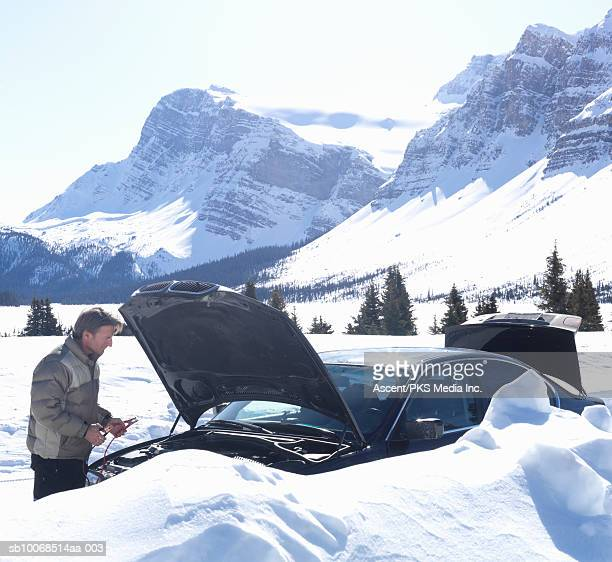 Man with broken car in snow