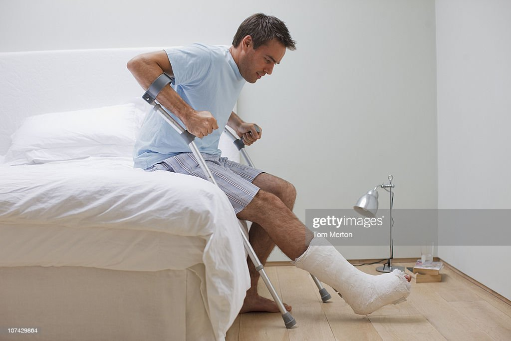 Man with broken leg trying to get up from bed : Stock Photo