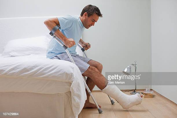 Man with broken leg trying to get up from bed