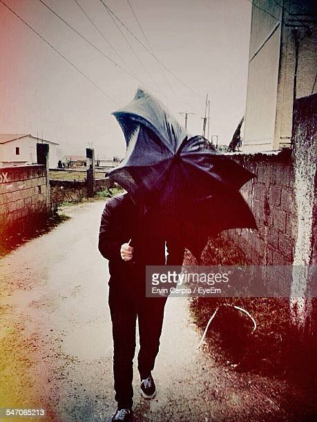 Man With Broken Umbrella On Street