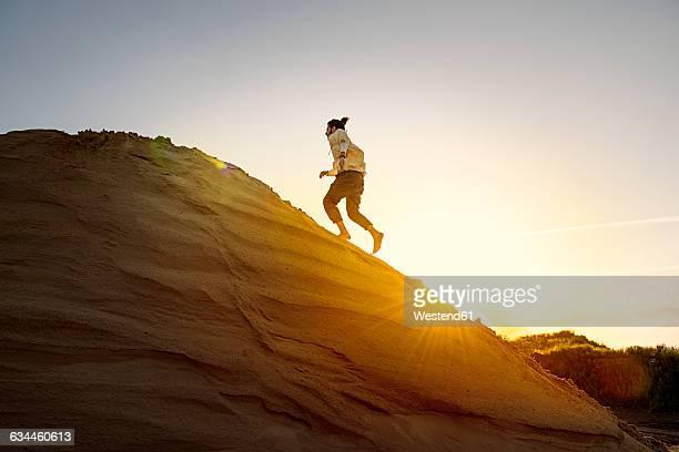 Man with bun running uphill