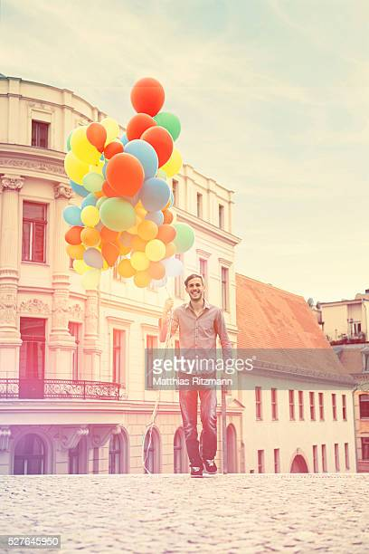 Man with bunch of colorful balloons walking on street