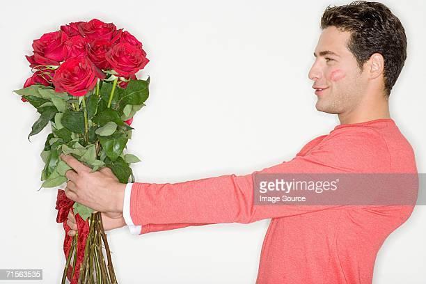 男性、束のバラとキスマーク