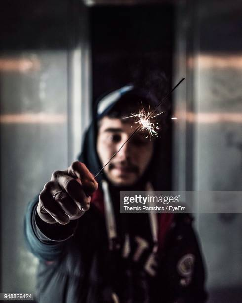 Man With Burning Sparkler Against Wall