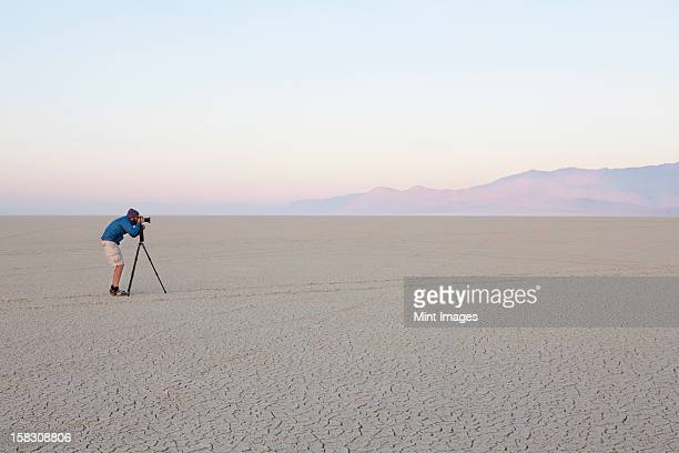 Man with camera and tripod on the flat saltpan or playa of Black Rock desert, Nevada.