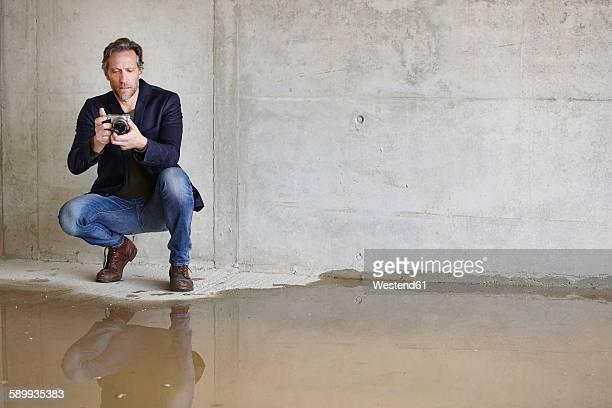 man with camera on construction site in unfinished building - beschädigt stock-fotos und bilder