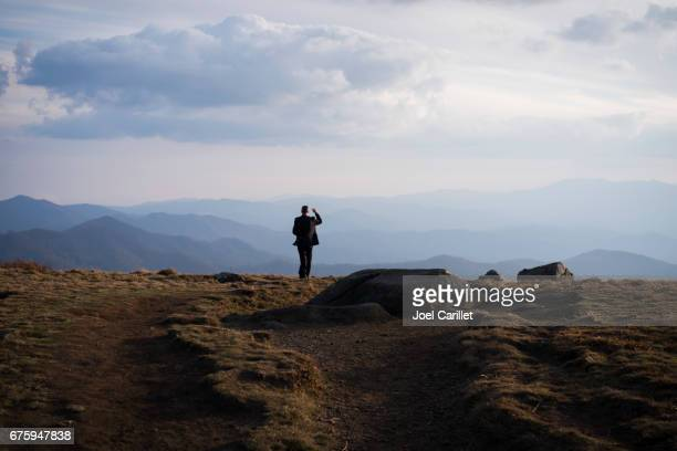 Man with camera standing at Round Bald on Roan Mountain