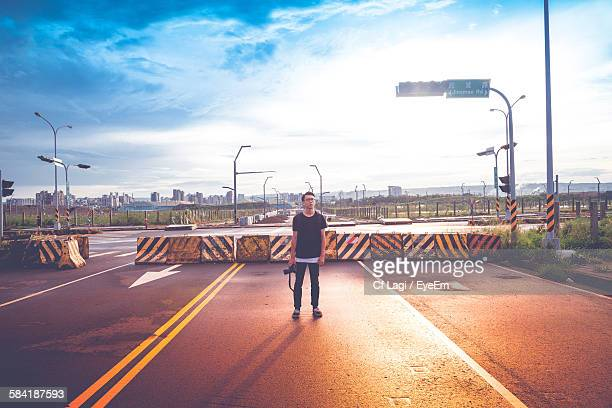 man with camera standing on road against sky - wide shot stock pictures, royalty-free photos & images