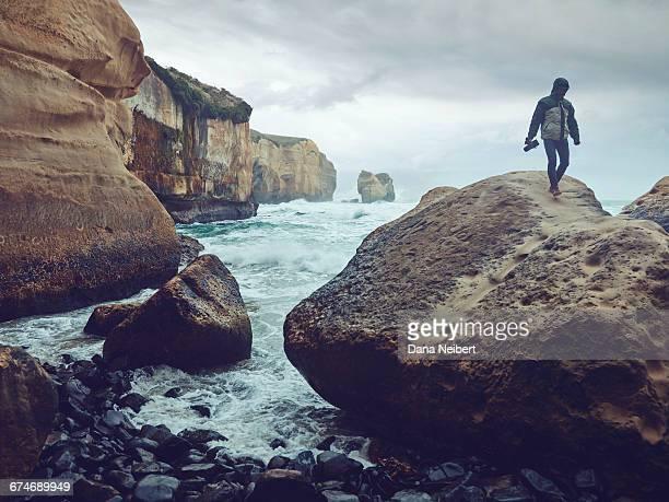 Man with camera walking on large boulder