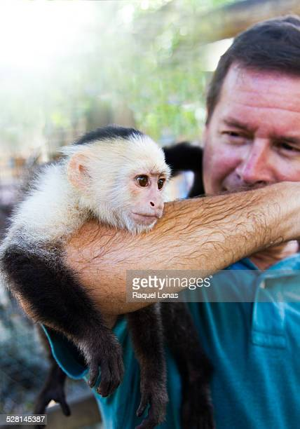 man with capuchin monkey - mono capuchino fotografías e imágenes de stock